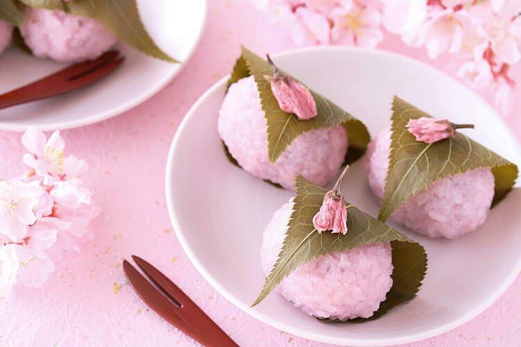 Bánh mochi anh đào có màu hồng bắt mắt và gói bằng lá cây.